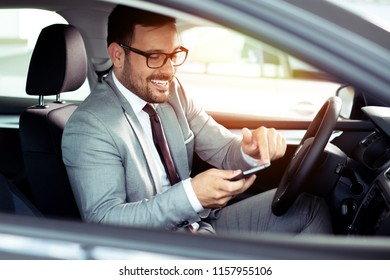 Young business man with phone in car
