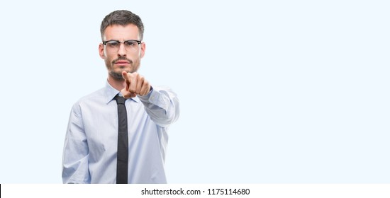Young business man pointing with finger to the camera and to you, hand sign, positive and confident gesture from the front