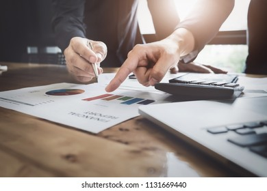 Young business man pointing graph chart with pathner  for analyze plans in this mounth. vintage tone.