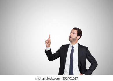 Young business man pointing up with his right hand.