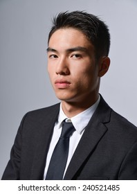 young business man portrait isolated on gray