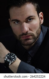 Young business man portrait with watch on his hand on dark background