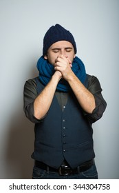 young business man praying with folded hands on the phone winter style clothes, studio shot isolated on the gray background