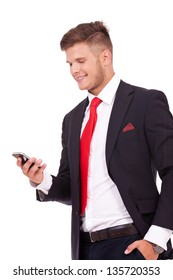young business man reading a message on his phone and smiling, with his hand in his pocket. isolated on white background