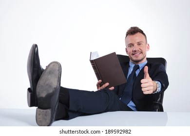 young business man recommending a book while reading it with his feet on the desk and smiling for the camera. on a light studio background
