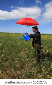 Young business man with a red umbrella and a blue watering can in a field