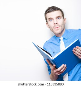 Young Business Man Researching Best Practice Strategies While Reading A Marketing Textbook On Copyspace Background