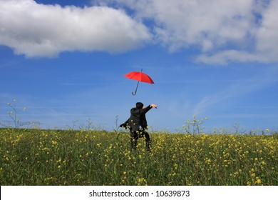 A young business man running after a flying umbrella