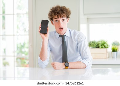 Young business man showing smartphone screen at the office scared in shock with a surprise face, afraid and excited with fear expression