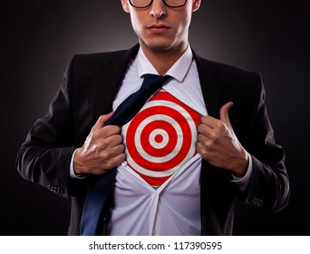 Young business man showing a target under his shirt on dark background