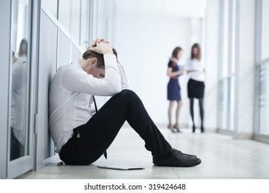 young business man sitting against glass wall in crisis moment