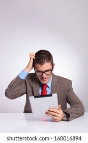 young business man sitting at the desk with a tablet in his hand and scratching his head while reading something. on a gray background