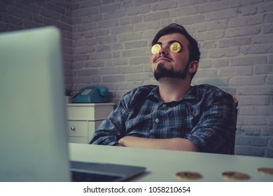 Young business man sitting at his computer imagining money and bitcoin rolling in to make him rich