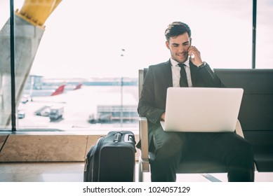 Young business man sitting on the computer and mobile phone with the suitcase at the airport waiting for the flight