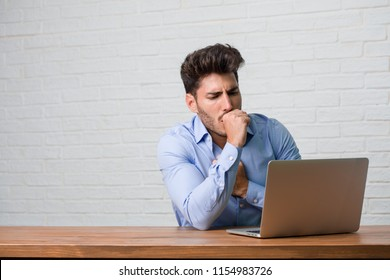 Young business man sitting and working on a laptop with a sore throat, sick due to a virus, tired and overwhelmed