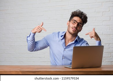 Young business man sitting and working on a laptop proud and confident, pointing fingers, example to follow, concept of satisfaction, arrogance and health