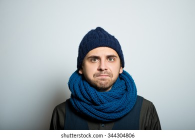 young business man with a sour face, winter style clothes, studio shot isolated on the gray background