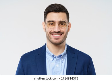 Young business man standing close to camera, isolated on gray background, looking through round glasses, smiling happily, feeling relaxed and confident