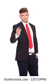 young business man standing with a hand in a pocket and holding a marker with the other, writing on an imaginary screen while looking at the camera with a serious look. isolated on white background