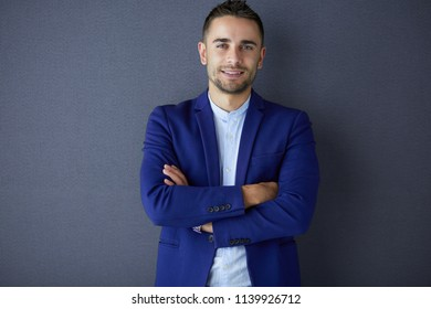 Young business man standing isolated on grey background