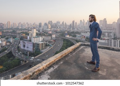 young business man standing on a roof and looking at city