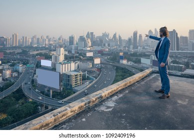 young business man standing on a roof and looking and Finger pointing to the city