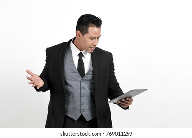 Young business man standing playing tablet on white background