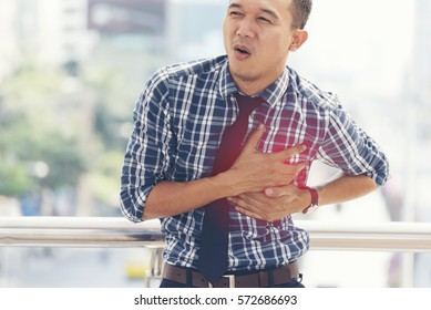 Young business man so stress with Heart Broken. Chest pained seem to be he will get heart attack from disease. Healthcare Medical Concept.