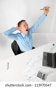 Young business man stretching his arms while yawning
