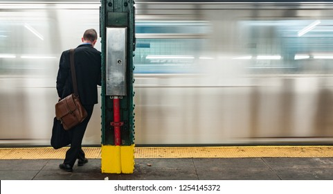 Young Business man at subway station stop waiting for the train to stop, blurry motion blur moving train background