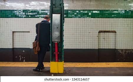 Young Business man at subway station stop waiting for the train.