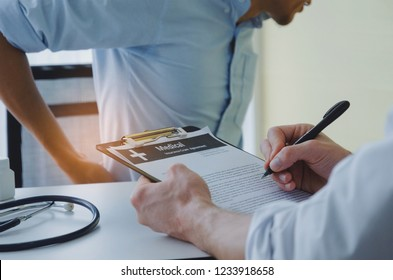 young business man suffering from backache meet doctor writing prescription on clipboard with stethoscope on desk in hospital, office syndrome, health care, medical, medicine, pharmacy concept