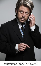 Young business man in suit calling with mobile phone