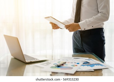 Young business man with suit and necktie working on digital tablet and notebook while standing in front of the big window in office or cafe
