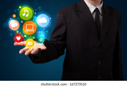 Young business man in suit presenting colorful technology icons and symbols