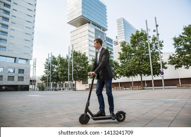 Young business man in a suit riding an electric scooter on a business meeting, office buildings, scooter, businessman