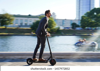 Young business man in a suit riding an electric scooter on a business meeting. Ecological transportation concept