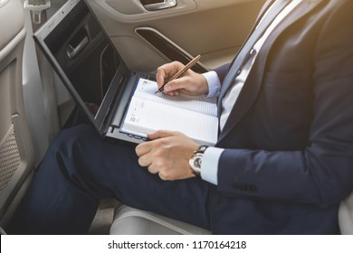a young business man in a suit is sitting in the back seat of a business car with a laptop and a notebook, business negotiations