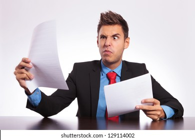 young business man at the table reading something unbelievable and making a weird face