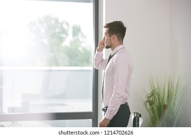 Young business man taking a phone call in the office and looking out the window