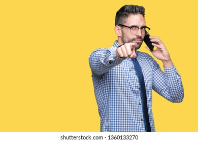 Young business man talking on the phone over isolated background pointing with finger to the camera and to you, hand sign, positive and confident gesture from the front