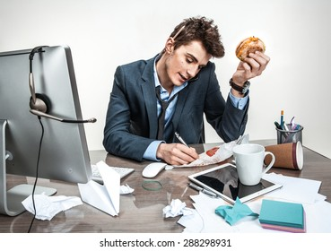 Young business man talking on the phone and writing down at his working place