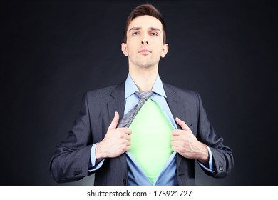 Young business man tearing apart his shirt revealing  superhero suit, on dark background