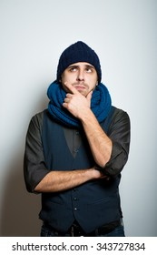 a young business man thinking, winter style clothes, studio shot isolated on the gray background