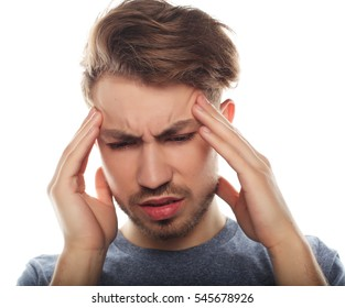 Young business man touching his head and keeping eyes closed