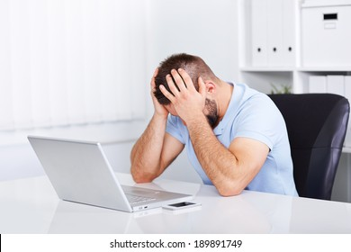 Young business man under stress with headache and migraine