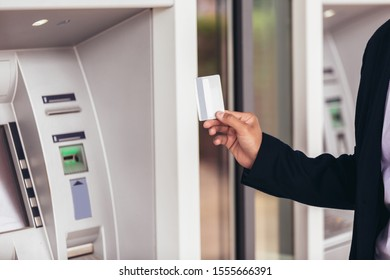 Young business man using ATM. Person using credit card to withdrawing money from atm machine.