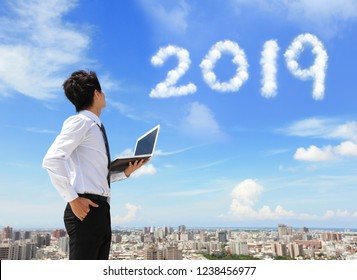 Young business man using laptop and look to 2019 year text with blue sky