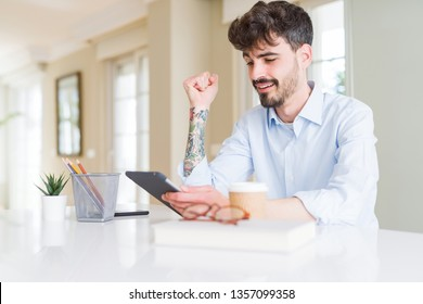 Young business man using touchpad tablet screaming proud and celebrating victory and success very excited, cheering emotion