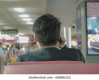 young business man is waiting for the flight at the waiting gate